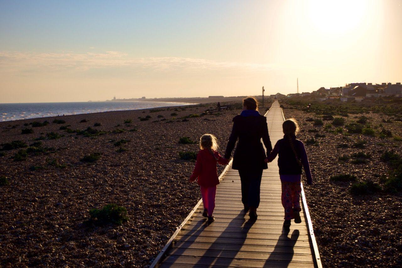 A mother and her children walking on the Shoreham Beach boardwalk near sunset